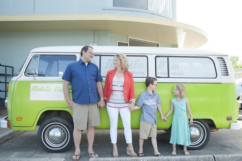 family posing in front of VW bus