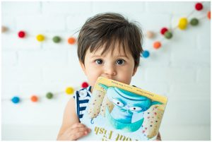 Baby Boy Chewing On Book During Photoshoot For First Birthday